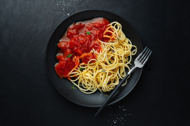 Espaguetis con salsa de tomate en un plato oscuro sobre una mesa oscura. vista superior.