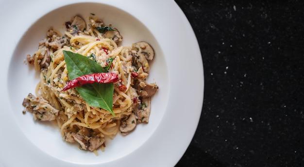 Espaguetis salteados con pescado salado, especias tailandesas y chile seco, en un plato blanco