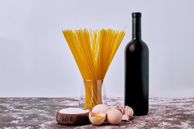 Espaguetis secos crudos con harina y huevos en mesa de madera.