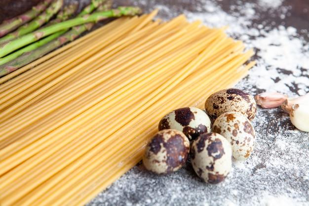 Espaguetis de vista de ángulo alto con espárragos, huevos y ajo sobre fondo oscuro con textura. horizontal