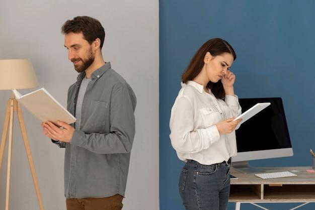 Espalda con espalda, hombre, con, libro, y, mujer, con, tableta