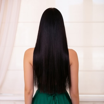 Espalda femenina con cabello largo y recto morena