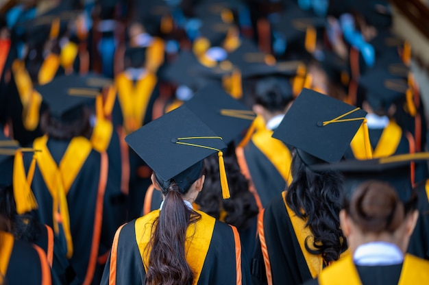 La espalda de los graduados caminan para asistir a la ceremonia de graduación en la universidad.