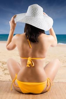 Espalda retrato de bonita chica en una playa con bikini amarillo