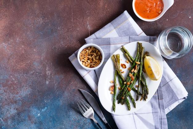 Espárragos asados en aceite de oliva con nueces trituradas y salsa. comida vegetariana.