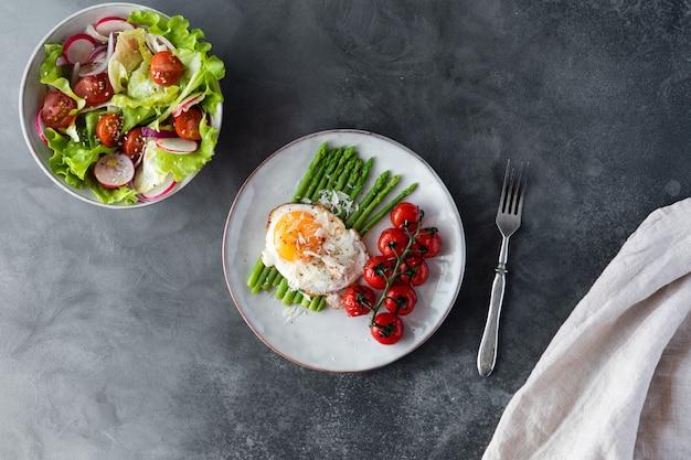 Espárragos blanqueados, huevo frito, tomates y sal en el tazón, vista superior.