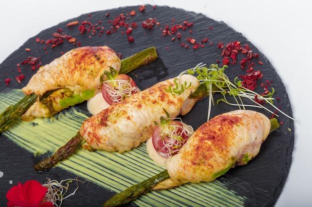 Espárragos enrollados en tocino a la parrilla servidos con salsa en un plato oscuro