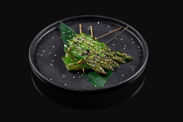 Espárragos a la plancha con semillas de sésamo en una elegante placa de cerámica negra sobre una superficie negra. plato de vegetetirian. foto del menú. de cerca
