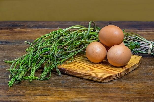 Espárragos silvestres y huevos en tabla de cortar