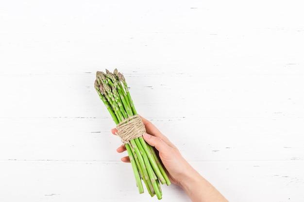 Espárragos verdes frescos en manos de mujer
