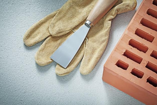 Espátula de construcción de guantes protectores de ladrillos naranjas sobre hormigón