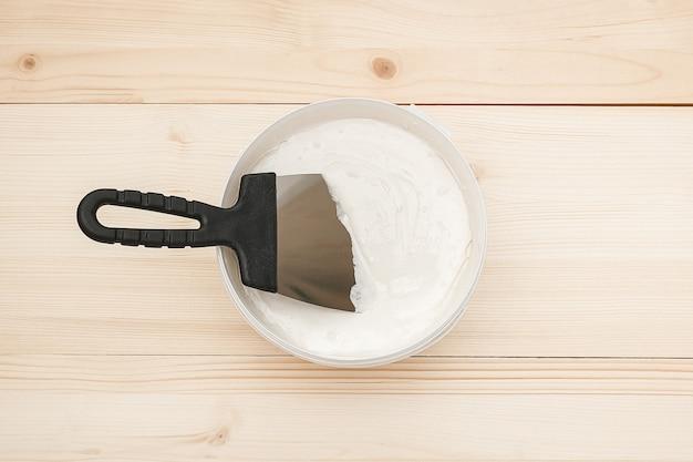 Espátula y un cubo de masilla blanca sobre tablas de madera