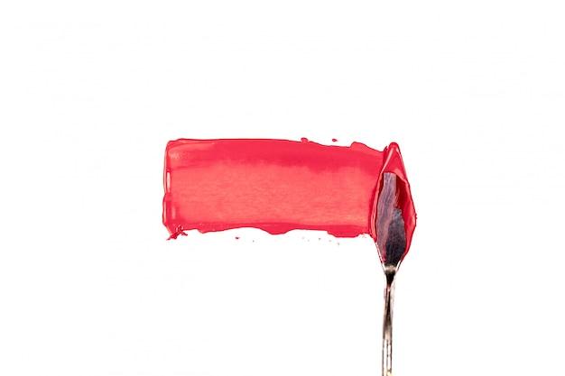 Una espátula de pintura aislada sobre un fondo blanco pintando un rojo