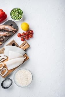 Especialidades de marisco crudo fresco y arroz para paella española sobre fondo de textura blanca, plano con espacio de copia