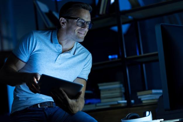 Especialista en acción. hombre inteligente brillante inteligente pasando la noche en la oficina