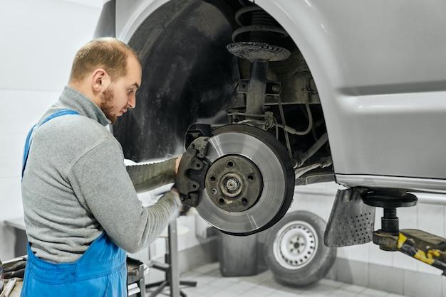 Especialista en automóviles que cambia los neumáticos o las pastillas de freno en un automóvil levantado
