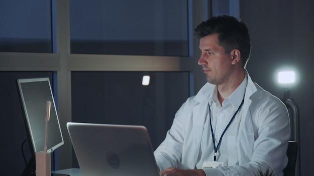 Especialista masculino en electrónica trabajando en la computadora en el laboratorio moderno. escritura profesional en código de programación