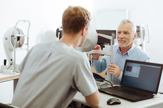 Especialista en ojos femeninos. oftalmólogo femenino vistiendo el uniforme sentado cerca de la computadora portátil hablando con su paciente