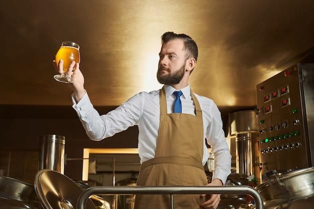 Especialista sosteniendo y mirando el vaso de cerveza