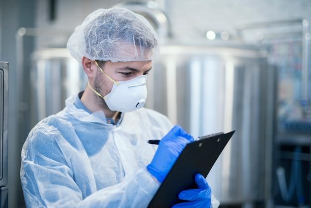 Especialista en tecnología con máscara protectora y redecilla sosteniendo la lista de verificación del portapapeles y escribiendo los resultados de producción