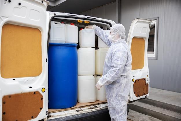 Especialista en trajes de materiales peligrosos que se preparan para la limpieza y desinfección de la epidemia de células de coronavirus