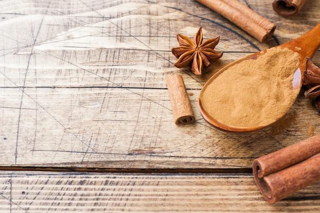 Especias aromáticas canela en rama y molida, anís estrellado sobre fondo de madera.