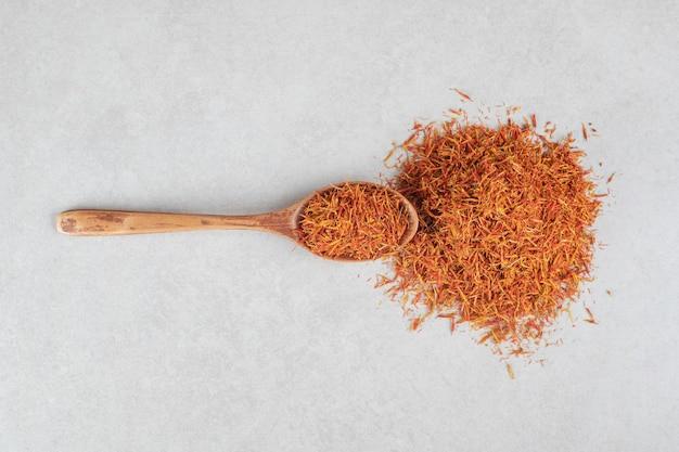 Especias de azafrán en una cuchara de madera sobre hormigón.