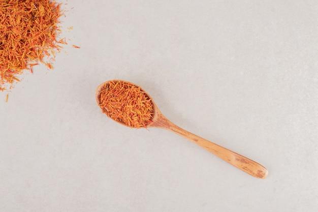 Especias de azafrán rojo en una cuchara de madera.