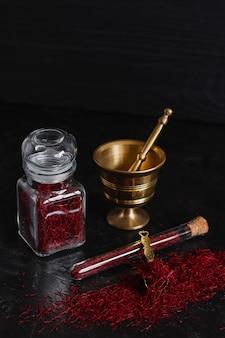 Especias de azafrán seco rojo orgánico crudo sobre fondo de madera en mortero de latón de metal vintage con mortero, frasco de vidrio y tubo.