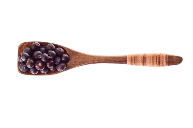 Especias bayas de enebro secas en cuchara de madera aislado sobre un fondo blanco, vista superior