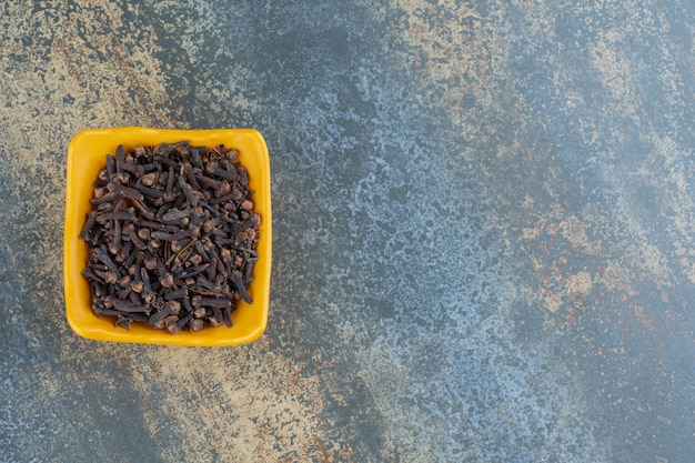 Especias de clavo seco en un tazón amarillo.