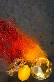 Especias de colores superiores con una botella de canela en rama de aceite de oliva y limón sobre negro