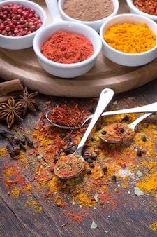 Especias coloridas en cucharas sobre fondo de madera oscura, vista superior