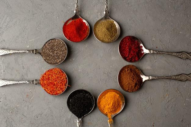 Especias coloridas picante diferente para la comida dentro de cucharas de plata en el piso gris