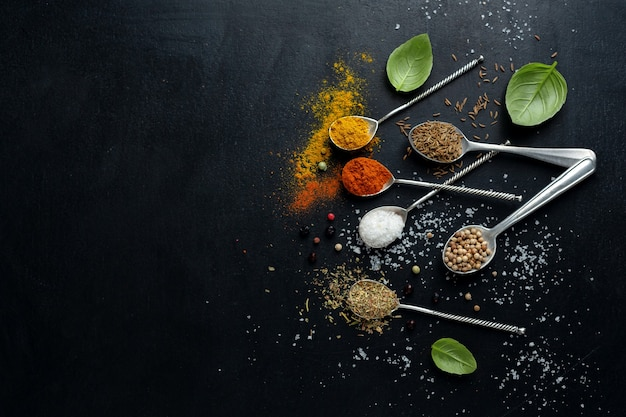 Especias coloridas sabrosas en cucharas sobre superficie oscura
