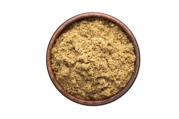 Especias de comino en polvo en un tazón de madera, aislado sobre fondo blanco. vista superior del condimento