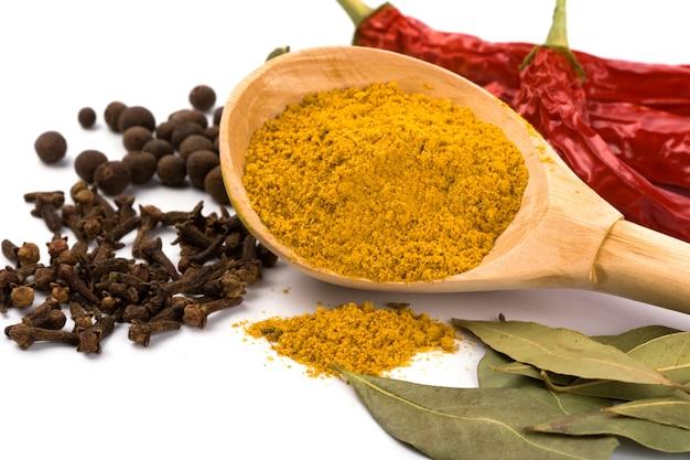 Especias: curry en cuchara de madera, pimienta, pimiento, clavo y laurel sobre fondo blanco