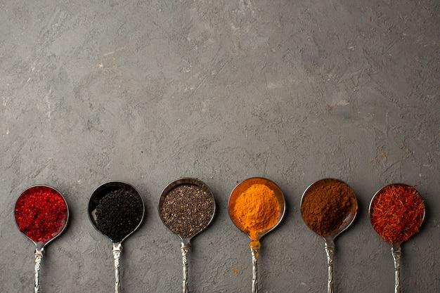 Especias forradas de diferentes colores calientes dentro de cucharas de plata una vista superior en el piso claro