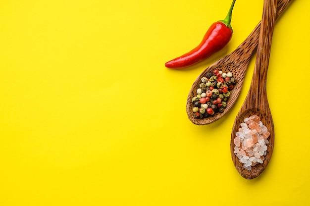 Especias fragantes en una cuchara y pimiento rojo aislado sobre fondo amarillo, vista superior. comida vegetariana orgánica, surtido de comestibles, productos ecológicos naturales, concepto de estilo de vida saludable