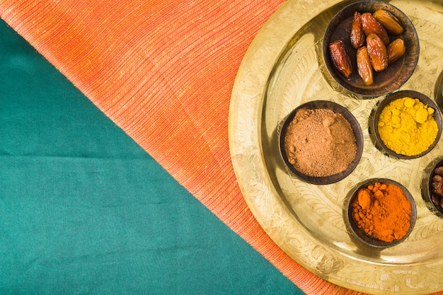 Especias y frutos secos en bandeja sobre textil.