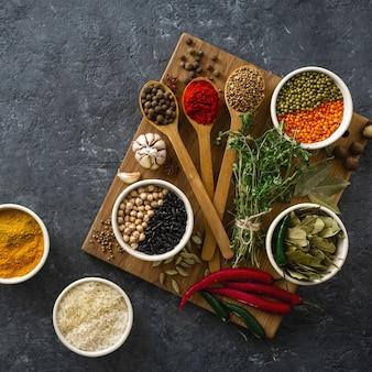 Especias, hierbas, arroz y varios frijoles y condimentos para cocinar en backgraund oscuro con vista superior del espacio de copia