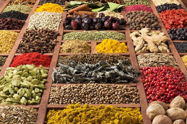 Especias y hierbas en bandejas de madera, vista superior. condimentos para cocinar deliciosas comidas.