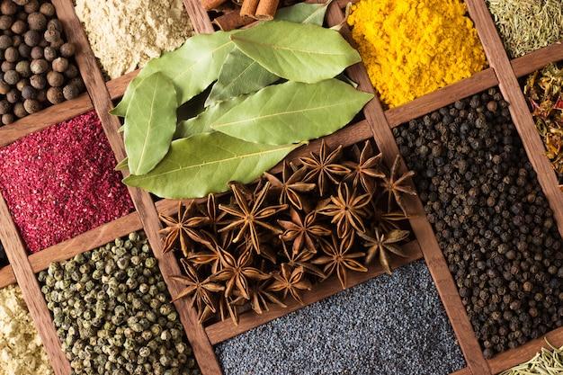 Especias y hierbas en cajas de madera. condimentos multicolores cerca