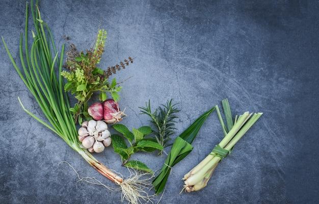 Especias y hierbas frescas naturales en placa negra en la cocina para alimentos ingredientes