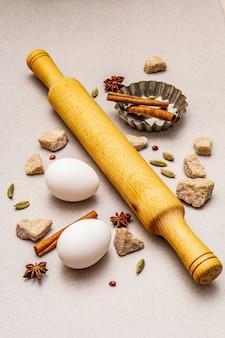 Especias, huevos, azúcar moreno, molde para hornear magdalenas y un rodillo. ligero