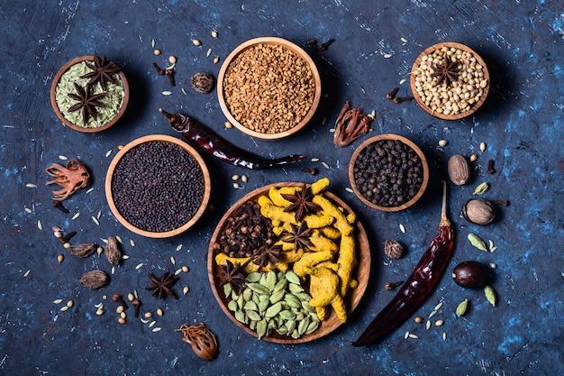 Especias indias enteras y calientes en cuencos de madera