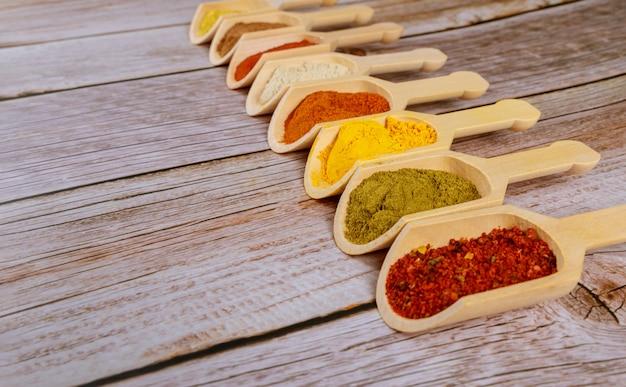 Especias molidas coloreadas en polvo en cucharas de madera