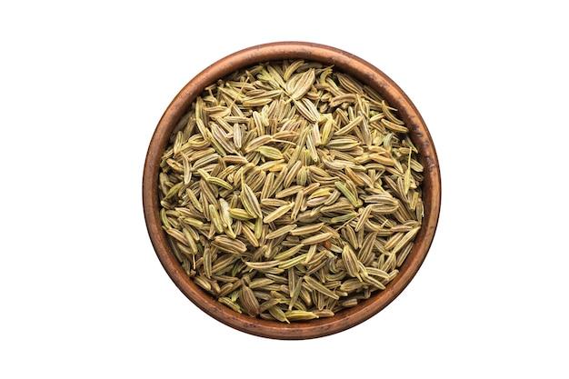 Especias de semillas de alcaravea en un tazón de madera, aislado en la pared blanca. vista superior del condimento
