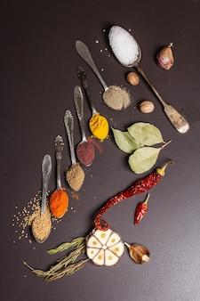 Especias surtidas en cucharas, hierbas secas y verduras.