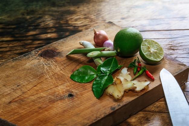 Especias tom yum que se colocan en una tabla de cortar de madera marrón y tienen una madera de color marrón oscuro.